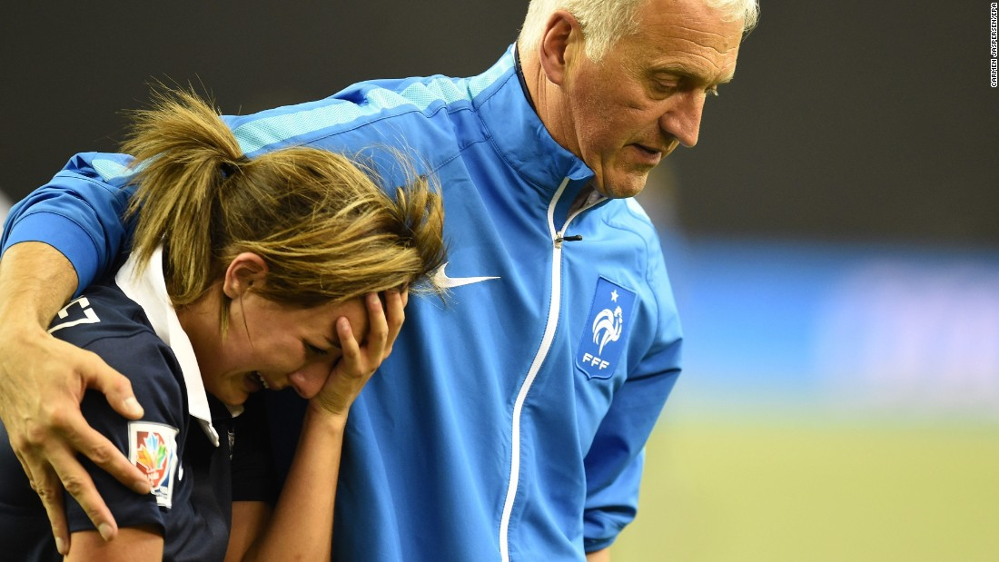 France's Claire Lavogez is consoled by head coach Philippe Bergeroo after she missed her penalty in the shootout.