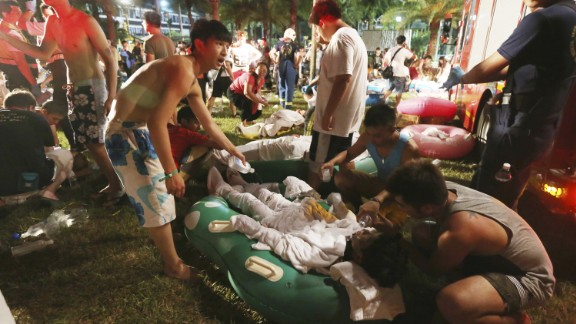 Emergency rescue workers and concert spectators tend to injured victims at the Formosa Water Park in New Taipei City, Taiwan, Saturday, June 27, after flammable powder apparently exploded in mid-air, according to the East Asian nation