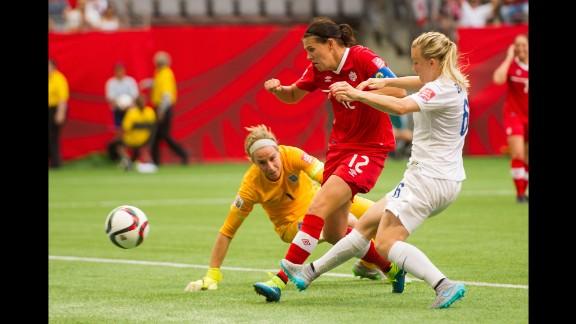 Canada's Christine Sinclair shoots the ball past English goalkeeper Karen Bardsley.