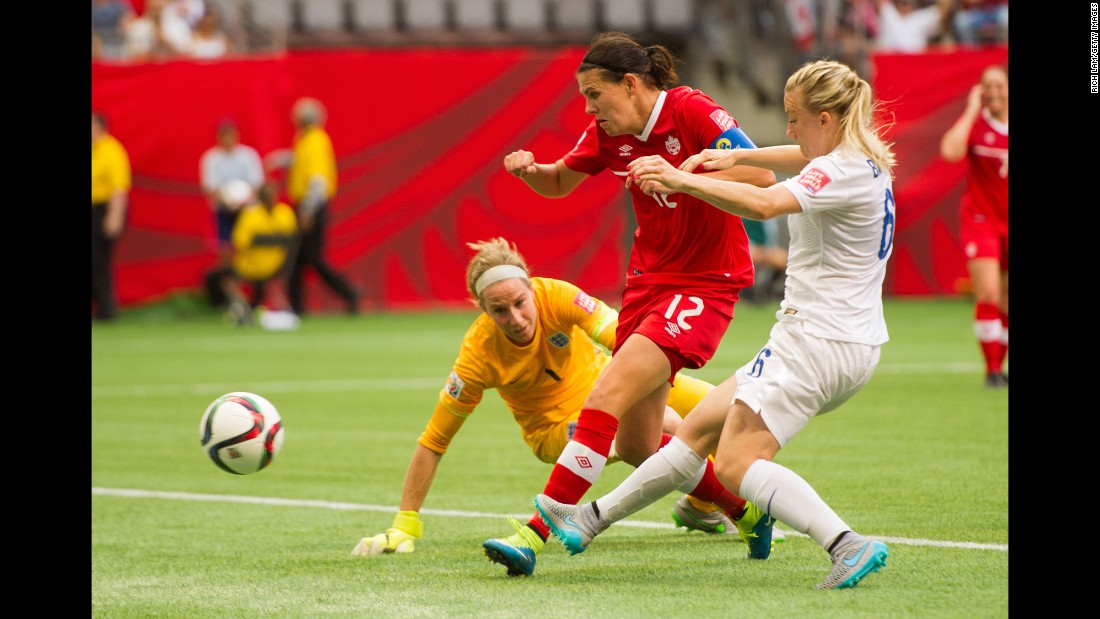 Canada's Christine Sinclair shoots the ball past English goalkeeper Karen Bardsley.