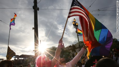 People wave a rainbow pride flag and an American flag during a gay pride celebration on June 27, 2015 in San Francisco.