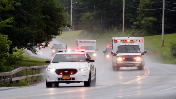 Police escort ambulances from an area where law enforcement officers were searching for Sweat on June 28.