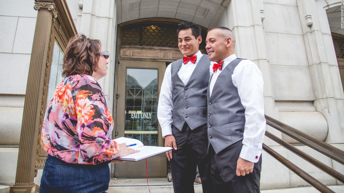 David Herrera-Santos, center, and Carlos Santos-Herrera, right, stand with wedding officiant Kimberley Boncella.