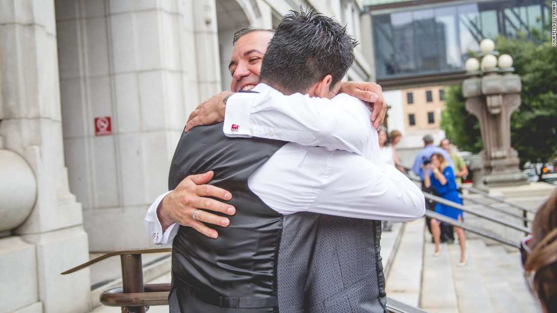 Carlos Santos-Herrera and David Herrera-Santos embrace on the courthouse steps.