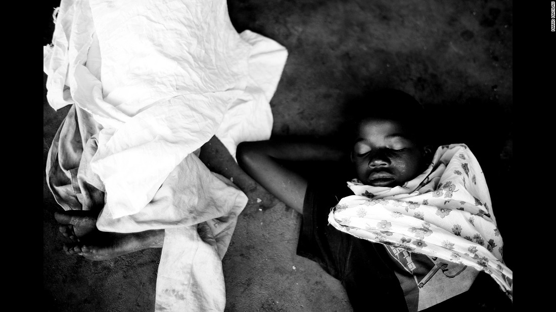 Two young boys sleep on a floor in a Maputo squatter settlement. Street children live as nomads, moving from one point to the next with nothing but a little bit of water and hand towels with which to wash cars.