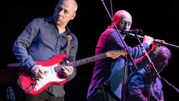 """Frontman Mark Knopfler, left, sang to the Live Aid audience about how to get """"money for nothing and chicks for free."""" Seen here, he performs in Paris in 2013."""
