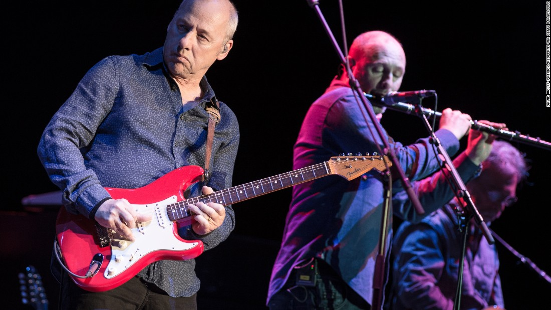 "Frontman Mark Knopfler, left, sang to the Live Aid audience about how to get ""money for nothing and chicks for free."" Seen here, he performs in Paris in 2013."