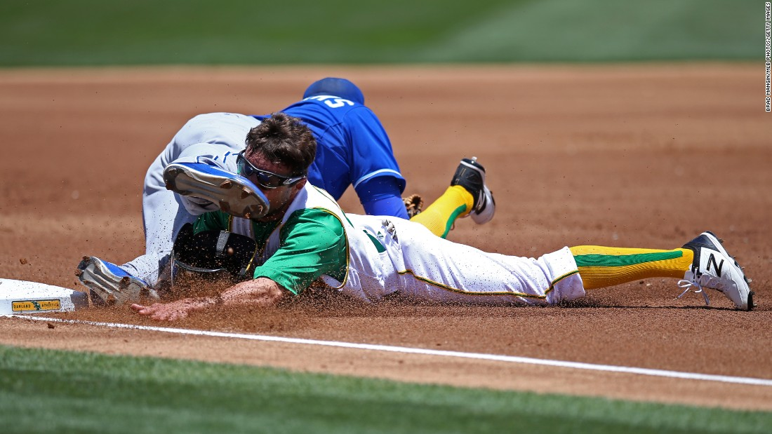 Oakland's Sam Fuld, bottom, slides safely into third base as Kansas City's Mike Moustakas tries to make the tag on Saturday, June 27.