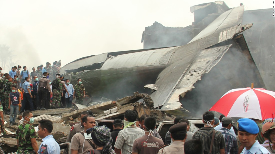 Military personnel inspect the wreckage.