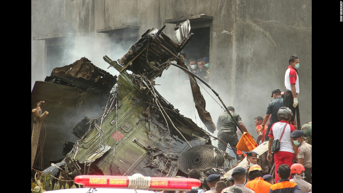 People search for victims around the wreckage.
