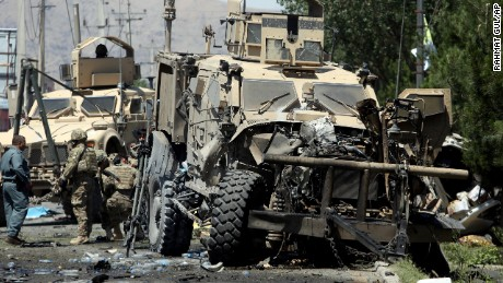NATO soldiers assess a wounded comrade at the site of a suicide attack on their convoy in Kabul.