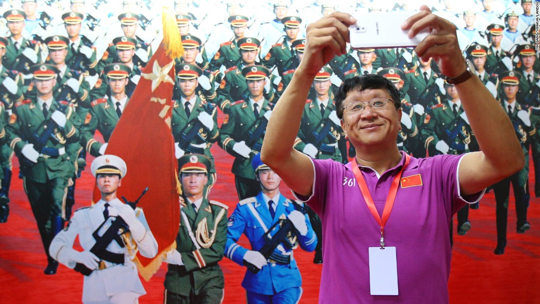 A man in Beijing takes a selfie in front of a poster of an honor guard on Saturday, June 27.