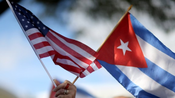 A protester holds an American flag and a Cuban one as she joins with others opposed to U.S. President Barack Obama's announcement earlier in the week of  a change to the United States Cuba policy stand together at Jose Marti park on December 20, 2014 in Miami, Florida. President Obama announced a move toward normalizing the relationship with Cuba after a swap of prisoners took place.