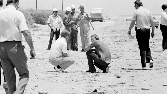 """David Brooks, 18, right, squats on the beach with a law enforcement official as police search for bodies in High Island, Texas, in 1973. Brooks was implicated with Elmer Wayne Henley and Dean Corll, in the murders of at least 24 young men in a mass slaying case. """"Dean Corill would pick up kids, and once he had them in his house, he would incapacitate them and put them on what he called his """"death board"""" and rape and kill them,"""" according to Stephen G. Michaud, author of """"The Only Living Witness."""" Corll died in 1973."""