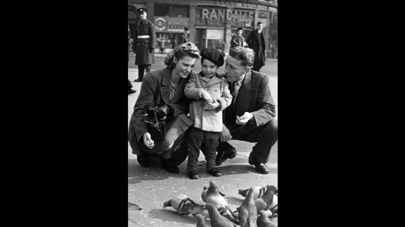 Charles Robert Watts, 2, feeds birds with his mother, Lillian, and his father, Charles, in London