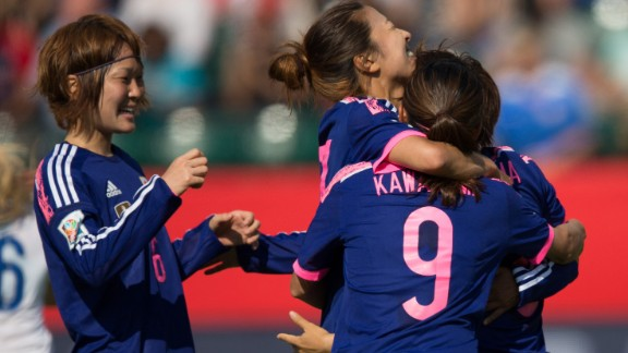 Japanese players celebrate their first-half goal against England during a Women