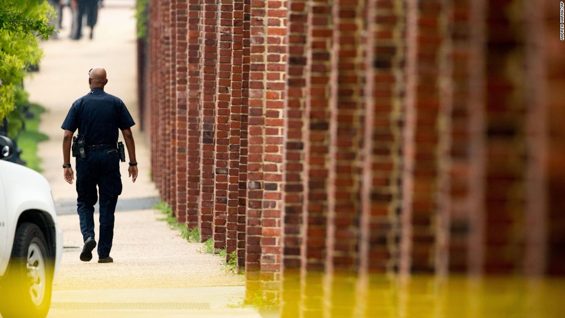 A police officer walks along the perimeter wall of the Navy Yard on July 2.