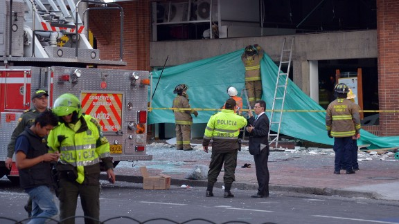 Colombian police officers and firefighters check the site of an explosion in the financial heart of Bogota.