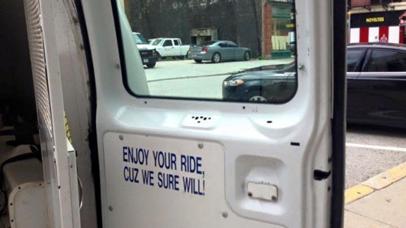 A sign inside the back door of a Baltimore police detainee transport vehicle warns about the ride