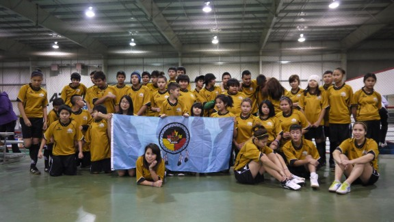 Team photo -- players from the communities of Fort Liard and Behchoko pose with the flag of Fort Liard at the Polar Cup.