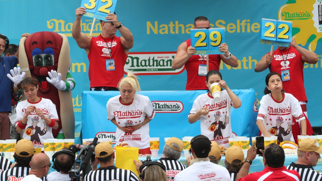 "The women's competition came down to Miki Sudo, second from left, and rival Sonya ""Black Widow"" Thomas, second from right. Sudo won for the second straight year, eating 38 hot dogs."