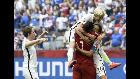 Lloyd is congratulated by teammates Hope Solo and Megan Rapinoe after scoring a goal.
