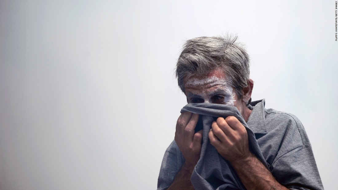 A demonstrator protects his face from teargas thrown by riot police.
