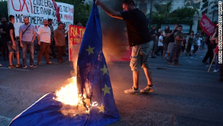 An anti-EU protester burns an EU flag in front of the European Comission offices in Athens on July 2, 2015.