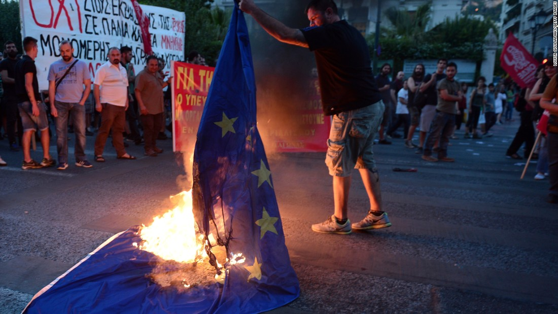 An anti-EU protester burns an EU flag in front of the European Commission offices.