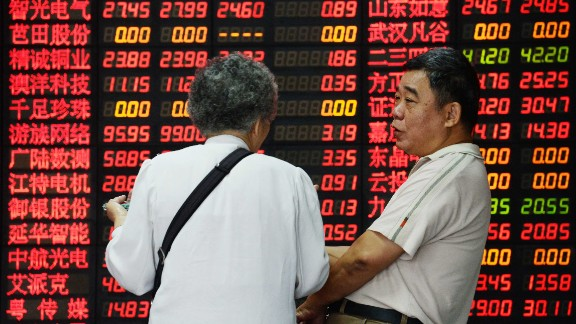 Investors talk in front of a board displaying share prices at a security firm in Shanghai on July 1, 2015. Shanghai shares closed down more than five percent on July 1, resuming their downward trajectory a day after recording their biggest gains in more than six years. AFP PHOTO CHINA OUT (Photo credit should read STR/AFP/Getty Images)