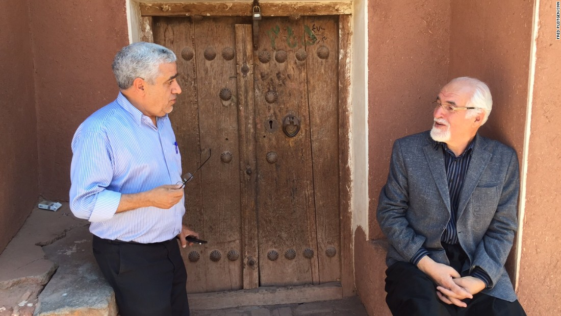 Reza Alirezai, pictured sitting down, is the head of the village council. He talks to another local resident.
