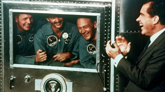 President Richard Nixon welcomes the astronauts back to Earth: from left, Armstrong, Collins and Aldrin. The astronauts were received by the President from their mobile quarantine unit, which was thought to help prevent the spread of contagions caught on the moon. The quarantine practice was discontinued a couple years later after Apollo 14