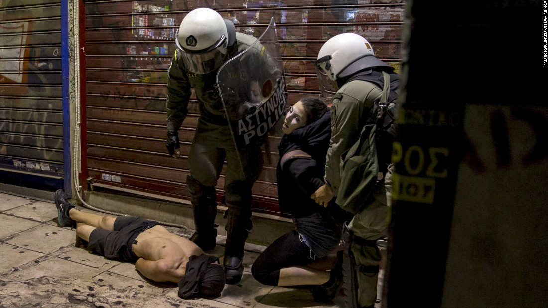 "Riot police detain masked youths during clashes in Athens, Greece, on Monday, July 6. Tension has been high in the cash-strapped country as it considers further austerity measures. Later in the week, the Greek government <a href=""http://money.cnn.com/2015/07/08/news/economy/greece-third-bailout/"" target=""_blank"">formally requested a third international bailout</a> to help pay its debts and prevent economic collapse and ejection from the euro."