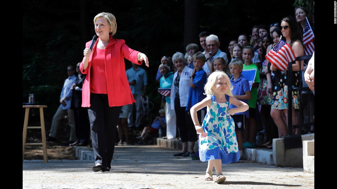 Louisa Hill, 3, walks onto a stage in Hanover, New Hampshire, as Democratic presidential candidate Hillary Clinton speaks on Friday, July 3.