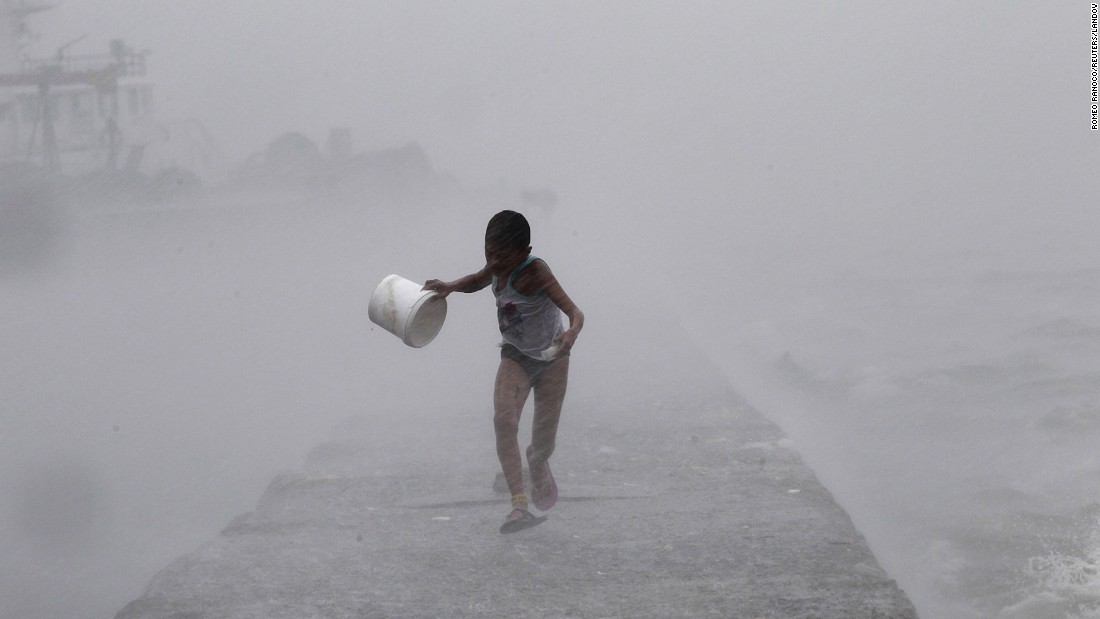 A boy runs in heavy rain as high waves crash along a breakwater in Manila, Philippines, on Monday, July 6. The extreme conditions were brought on by Typhoon Linfa.