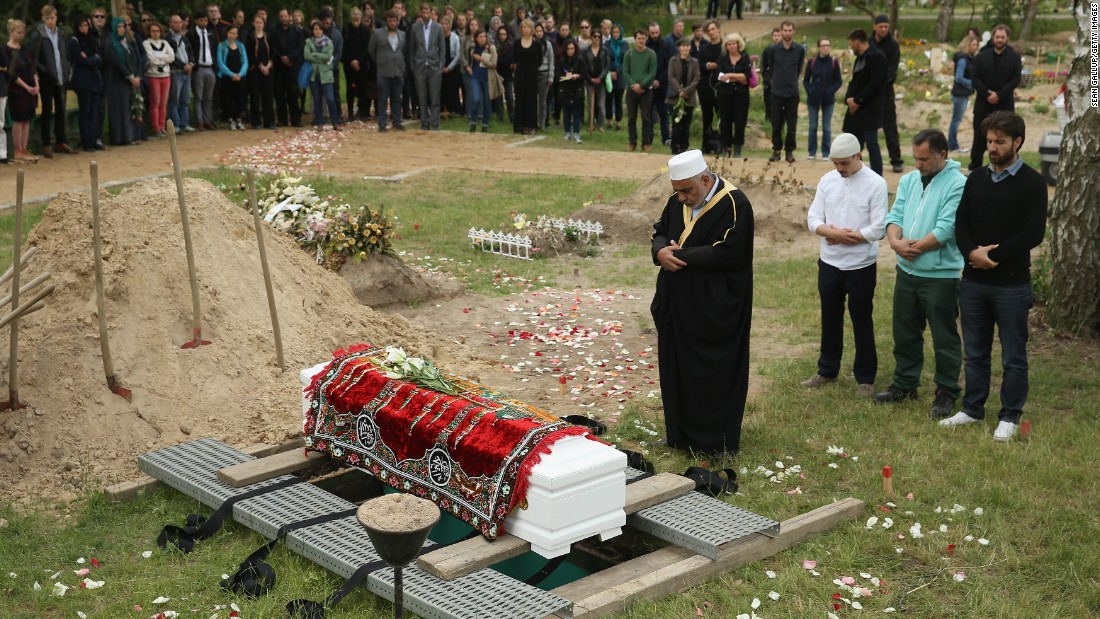 An imam leads a memorial service while standing next to a coffin, which, according to an artist group spokesman, contains the body of a female Syrian refugee who drowned in the Mediterranean in her attempt to reach Europe, in a reburial at Gatow cemetery on June 16, 2015 in Berlin, Germany. A German artist group called 'Political Beauty' ('Politische Schoenheit'), which had led the exhumation of the woman's body from Italy, organized the event as a form of protest against European Union refugee policy.