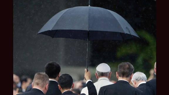 A member of the security detail holds an umbrella over Pope Francis upon his arrival in Asuncion on Friday, July 10.