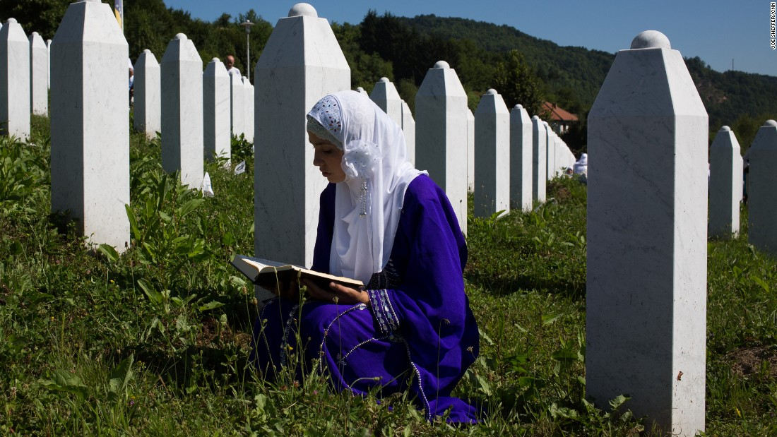 A girl reads the Quran at the site of her father's grave.