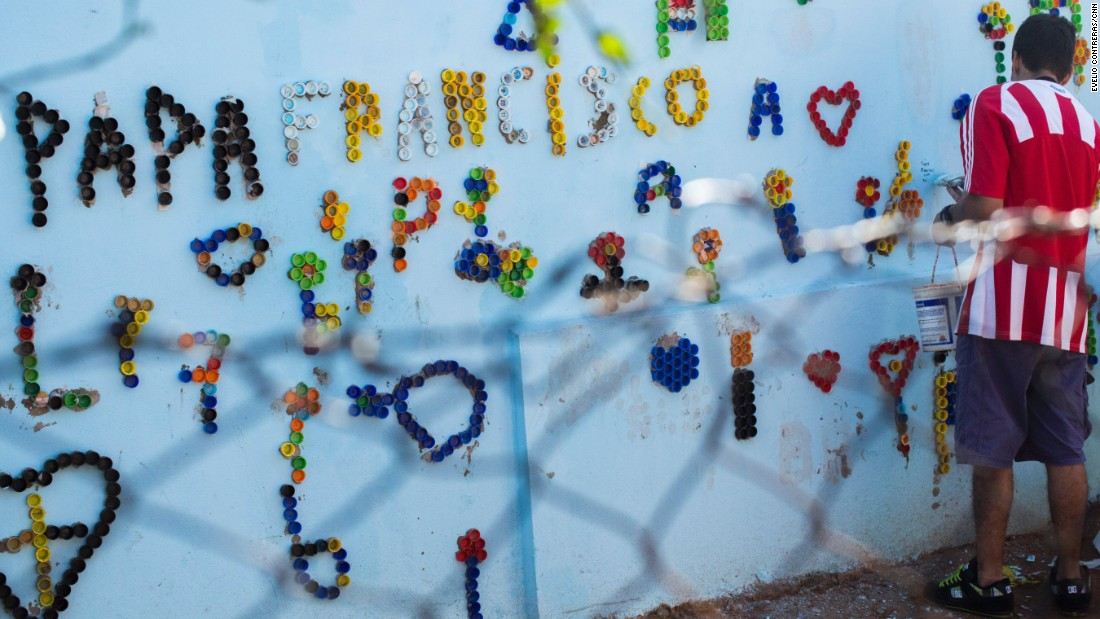 Neighbors paint the walls and write Pope Francis' name to celebrate his visit to Bañado Norte.