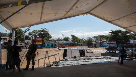 Volunteers decorate and prepare the stage for Pope Francis' arrival on Sunday, July 12. The area has been flooded countless times, leaving many homes in shambles, but people feel renewal knowing of the Pontiff's visit.