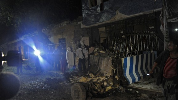 People gather at the scene of an explosion at the Weheliye hotel in Mogadishu on July 10, 2015.