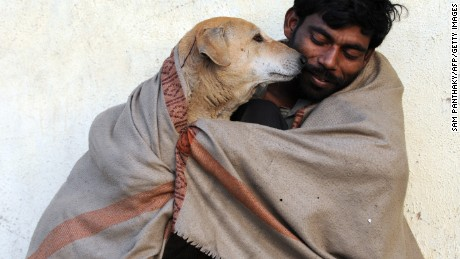 An Indian man shares his shawl with a stray dog in Ahmedabad on a cold morning on January 19, 2012.
