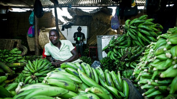 """A South Sudanese market trader sits in his shop where he sells imported bananas from Uganda. Another disease, called """"BXW,"""" has nearly destroyed Uganda's banana industry about a decade ago."""