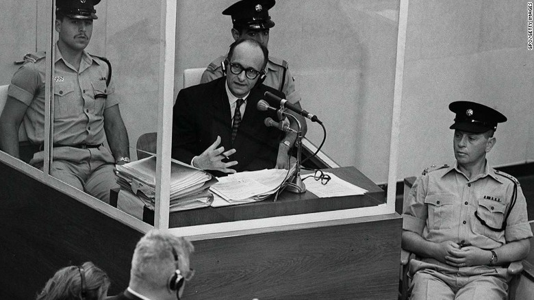 Eichmann stands in a protective glass booth flanked by Israeli police during his 1961 war crimes trial.