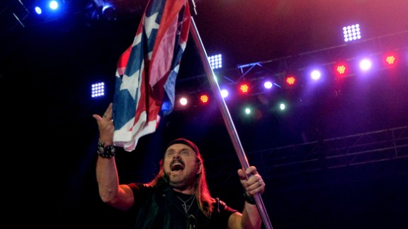 """Lynyrd Skynyrd trotted out the flag as a symbol of rebellion in the 1970s, as seen on a clip of the band performing """"Sweet Home Alabama"""" in 1975. The group's Gary Rossington told CNN in 2012 that it would stop using it, though Skynyrd soon brought it back. But now they give American flags more prominence."""