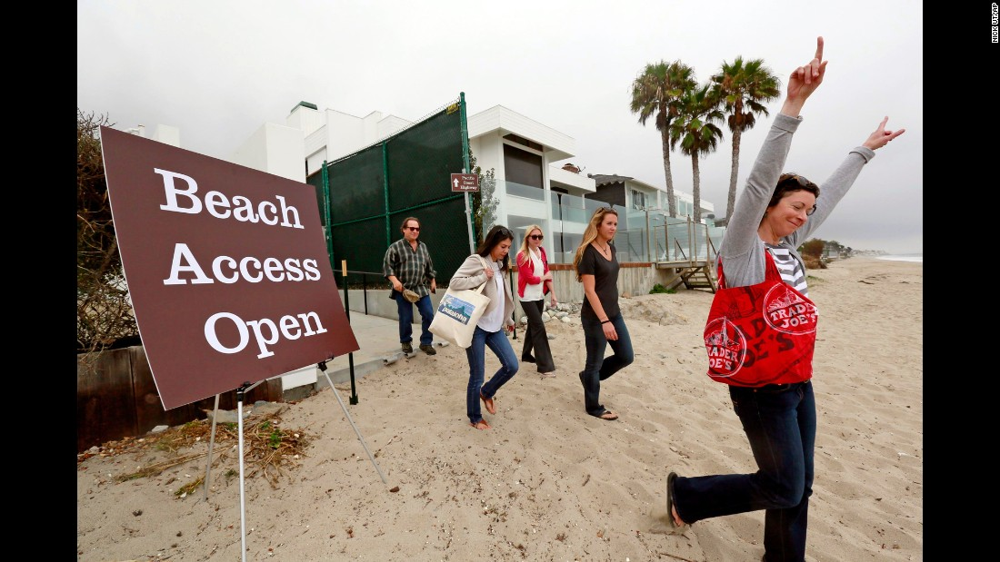 Beachgoers celebrate as they walk onto Billionaire's Beach after a ribbon-cutting ceremony in early July for the new path, which lies halfway between the original path by the pier and one near David Geffen's compound at the other end of the beach. The so-called Geffen gate opened in 2007 after the entertainment mogul lost a court fight to block access.