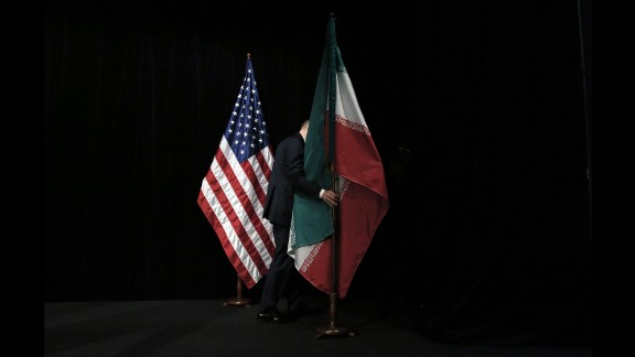 A staff removes the Iranian flag from the stage after a group picture with foreign ministers and representatives of Unites States, Iran, China, Russia, Britain, Germany, France and the European Union during the Iran nuclear talks at Austria International Centre in Vienna, Austria on July 14, 2015. Major powers clinched a historic deal aimed at ensuring Iran does not obtain the nuclear bomb, opening up Tehran