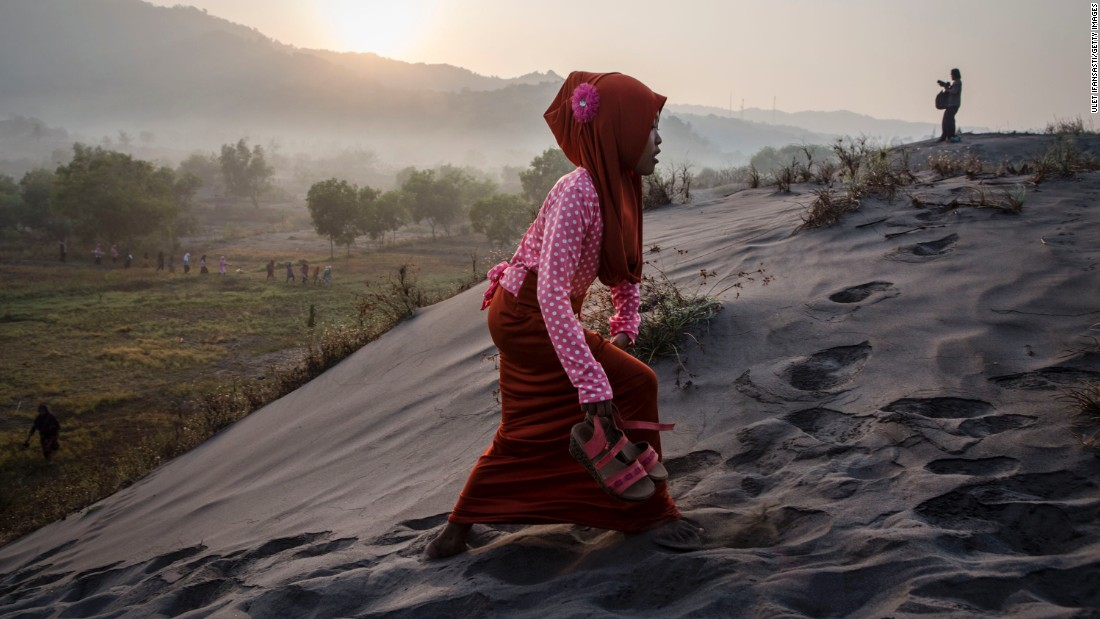 "An woman walks on a ""sea of sands"" at Parangkusumo Beach in Yogyakarta, Indonesia."
