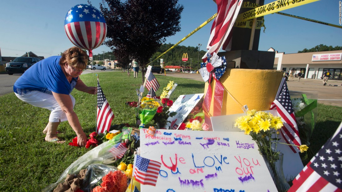 A woman places a balloon and flowers at a makeshift memorial outside the military recruiting center on Friday, July 17.