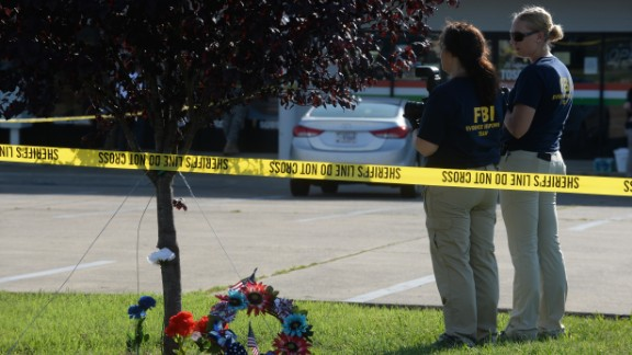 Members of the FBI gather evidence at the scene of the recruiting center shooting on July 16.